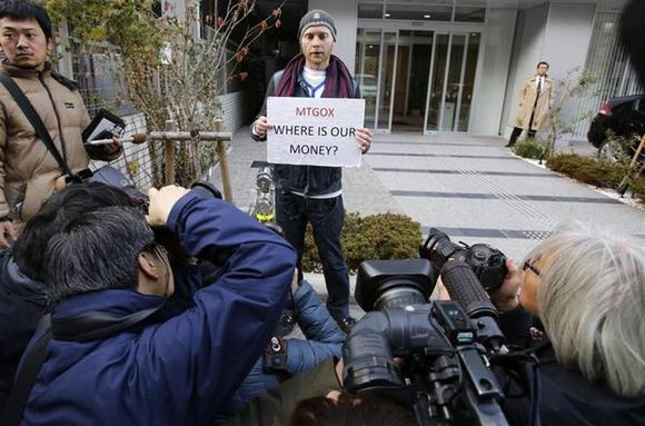 Kolin Burges (C), a self-styled cryptocurrency trader and former software engineer from London, holds a placard to protest against Mt. Gox, as photographers take photos of him in front of the building where the digital marketplace operator was formerly housed in Tokyo February 26, 2014. REUTERS/Toru Hanai