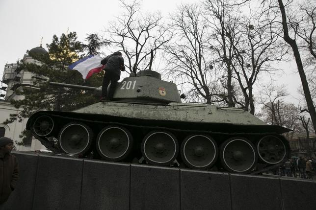 An ethnic Russian Ukrainian man holds the Crimea flag on top of an old Soviet tank during rallies near the Crimean parliament building in Simferopol February 26, 2014. REUTERS/Baz Ratner