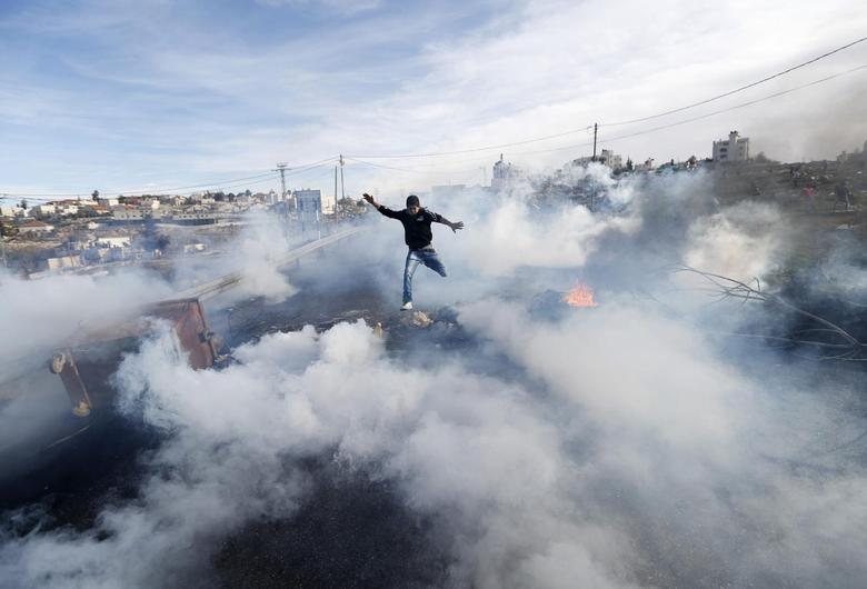 A Palestinian protester jumps as tear gas fired by Israeli soldiers rises during clashes in Jalazoun refugee camp near the West Bank city of Ramallah January 31, 2014 file photo. REUTERS/Mohamad Torokman
