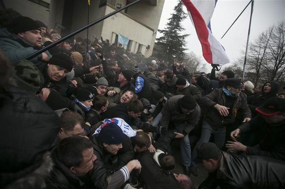 Ukrainian men help pull one another out of a stampede as a flag of Crimea is seen during clashes at rallies held by ethnic Russians and Crimean Tatars near the Crimean parliament building in Simferopol February 26, 2014. Thousands of pro-Russia separatists tussled with supporters of Ukraine's new leaders in Crimea on Wednesday as tempers boiled over the future of the region following the upheaval that swept away President Viktor Yanukovich. REUTERS/Baz Ratner