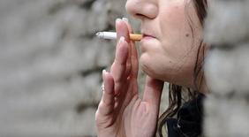 Женщина курит сигарету в Лондоне 6 мая 2009 года. Производитель сигарет British American Tobacco PLC нарастил базовую прибыль на 6 процентов в прошлом году благодаря увеличению рыночной доли. REUTERS/Toby Melville
