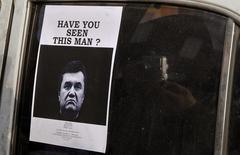 Мужчина фотографирует объявление о розыске бежавшего украинского президента Виктора Януковича на Майдане Незалежности в Киеве 24 февраля 2014 года. Россия укрыла Януковича, которого революционные власти объявили в розыск, надеясь отдать под суд в Гааге по обвинению в гибели десятков демонстрантов под пулями снайперов. REUTERS/Yannis Behrakis