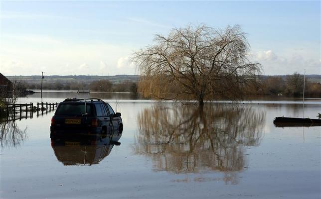 A semi submerged car is seen in urban landscape taken in the flooded Somerset village of Moorland February 16, 2014. REUTERS/Cathal McNaughton