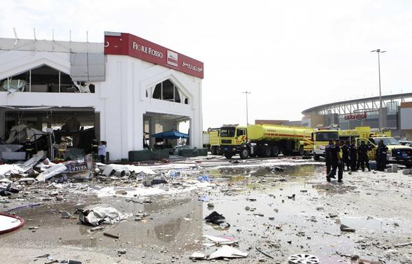 People stand among debris near a Turkish restaurant following a gas explosion in Doha February 27, 2014. Twelve people were killed, including two children, and about 30 wounded when the gas tank exploded at the Turkish restaurant in the Qatari capital off Doha on Thursday, authorities in the Gulf Arab state reported. REUTERS-Stringer