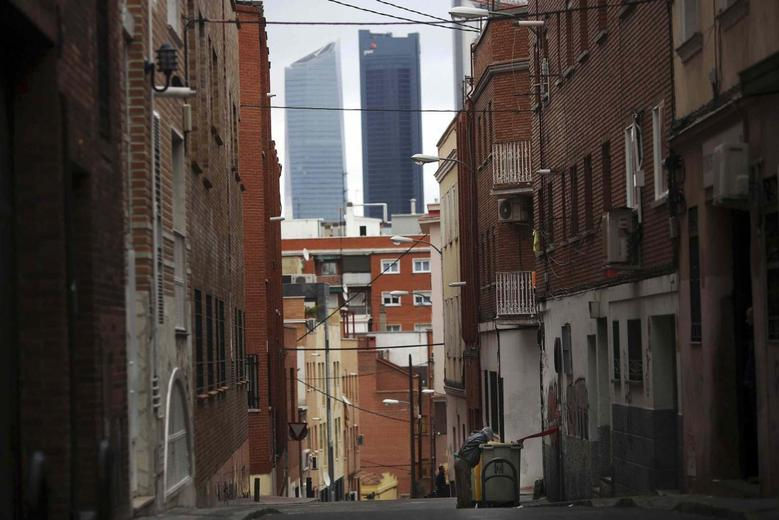 A man searches for food in a garbage container along a street, with the Four Towers business district pictured in the background, in Tetuan, Madrid, January 28, 2014. REUTERS/Susana Vera
