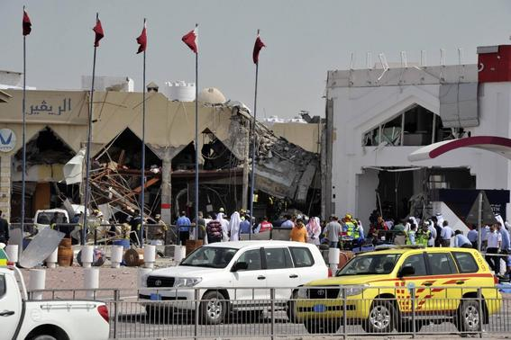 People stand amidst debris near a Turkish restaurant following a gas explosion in Doha February 27, 2014. Twelve people were killed, including two children, and about 30 wounded when a gas tank exploded at the Turkish restaurant in the Qatari capital off Doha on Thursday, authorities in the Gulf Arab state reported. REUTERS-Stringer