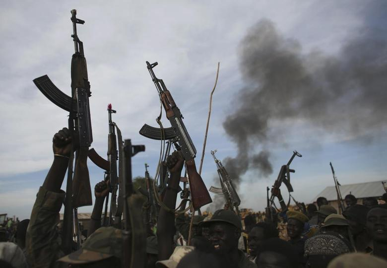 Rebel fighters hold up their rifles as they walk in front of a bushfire in a rebel controlled territory in Upper Nile State February 13, 2014. REUTERS/Goran Tomasevic