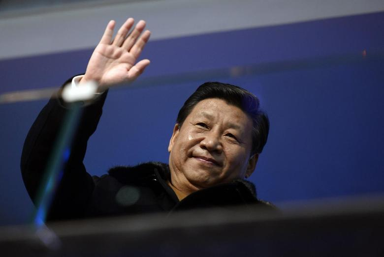 China's President Xi Jinping waves from the presidential tribune at the opening ceremony of the 2014 Winter Olympics in Sochi, February 7, 2014. REUTERS/Lionel Bonaventure/Pool