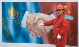 Китайский рабочий стоит у постера во время запуска казахского участка газопровода Центральная Азия-Китай близ Алма-Аты 12 декабря 2009 года. Казахстанская государственная газотранспортная компания Казтрансгаз заняла $700 миллионов у Банка развития Китая, чтобы достроить магистральный газопровод Бейнеу-Бозой-Шымкент, по которому казахский и туркменский газ поставляется на юг страны и транзитом в Китай. REUTERS/Shamil Zhumatov