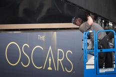 A man sets a digital display above the red carpet during preparations for the 86th Academy Awards in Hollywood, California February 26, 2014. REUTERS/Adrees Latif