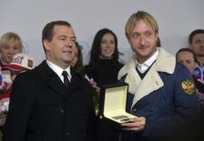 Russia's Prime Minister Dmitry Medvedev and figure skating gold medal winner Evgeni Plushenko (R) attend a ceremony to present automobiles to the Sochi 2014 Winter Olympics prize-holders representing Russia, by the Kremlin wall in central Moscow, February 27, 2014. REUTERS/Artem Zhitenev/RIA Novosti/Pool