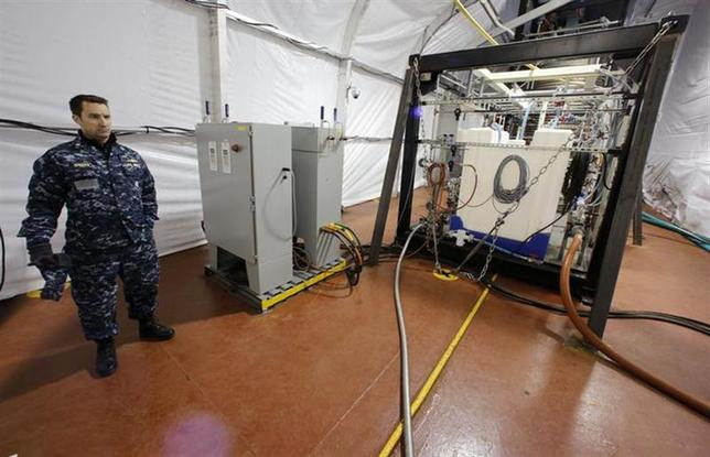 The Field Deployable Hydrolysis System used to destroy and neutralize chemical weapons is watched by U.S. Navy Commander Bill Speaks as it sits aboard the MV Cape Ray before its deployment from the NASSC0-Earl Shipyard in Portsmouth, Virginia, January 2, 2014. REUTERS/Larry Downing