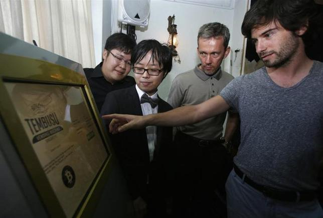 Tembusu Terminals' partners (back L-R) Jarrod Luo, Peter Peh Sik Wee and Andras Kristof watch as a volunteer demonstrates the use of their Bitcoin vending machine during a launch at a pub in Singapore February 27, 2014. REUTERS/Edgar Su