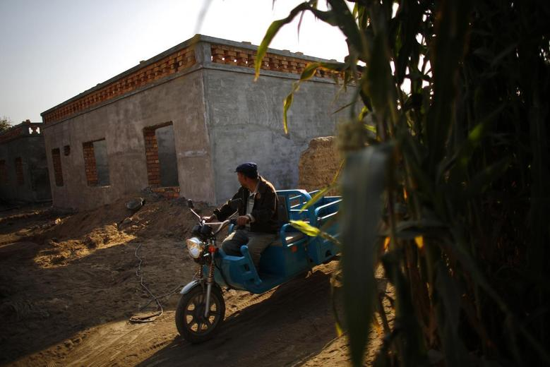 An ethnic Uighur man drives a tricycle near a construction site for new houses in Turpan, Xinjiang province October 31, 2013. REUTERS/Carlos Barria
