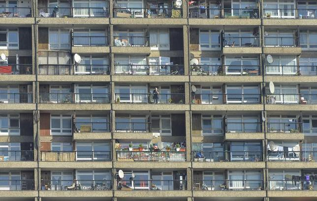 A man stands on a balcony (C) in a residential high rise block of flats in North Kensington in central London October 8, 2013. REUTERS/Toby Melville