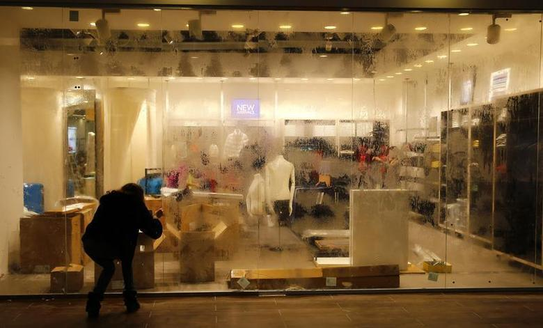 A woman tries to clean the window of an unopened shop that is being prepared in a mall at the village of Esto Sadok at the Rosa Khutor alpine resort near Sochi, February 2, 2014. REUTERS/Kai Pfaffenbach