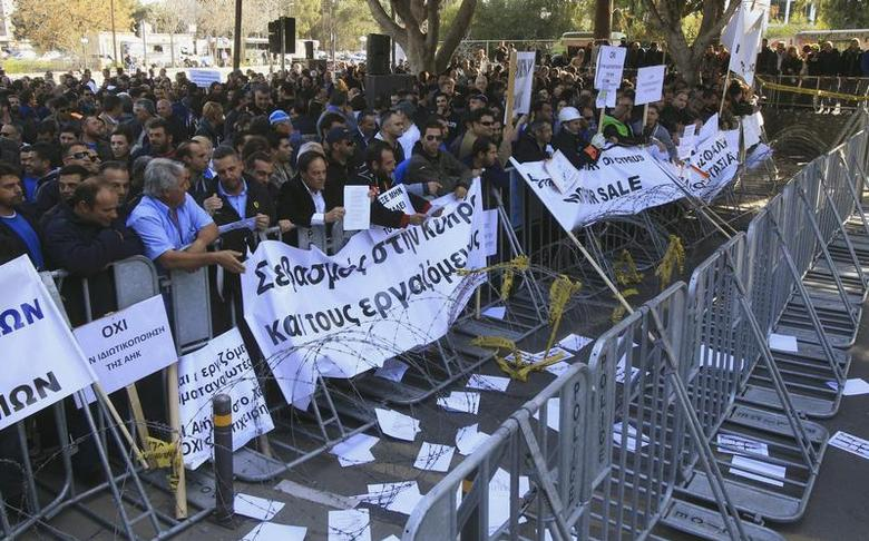 Demonstrators hold signs and banners outside Cyprus's parliament as they protest plans by the government to sell off state-owned enterprises, in Nicosia February 27, 2014. REUTERS/Andreas Manolis