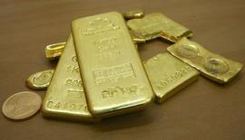 Золотые слитки и монеты в ювелирном магазине в индийском городе Чандигарх 4 ноября 2009 года. Цены на золото снижаются, но завершат февраль наиболее значительным повышением с июля за счет опасений за рост американской экономики и политического кризиса на Украине. REUTERS/Ajay Verma