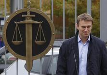 Российский оппозиционный лидер Алексей Навальный прибывает в суд в Москве 9 октября 2013 года. Басманный суд Москвы приговорил к домашнему аресту как минимум на два месяца уже отбывающего административное наказание оппозиционного лидера Алексея Навального, запретив популярному блоггеру пользоваться интернетом и общаться с прессой. REUTERS/Maxim Shemetov