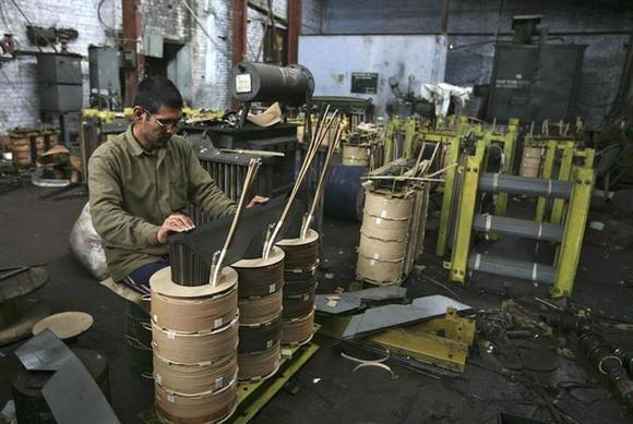 An employee works on a transformer inside an electrical appliances manufacturing unit on the outskirts of Jammu February 28, 2014. REUTERS/Mukesh Gupta/Files