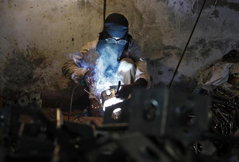 An employee works inside a electrical equipments manufacturing unit in New Delhi December 2, 2013. REUTERS/Anindito Mukherjee/Files