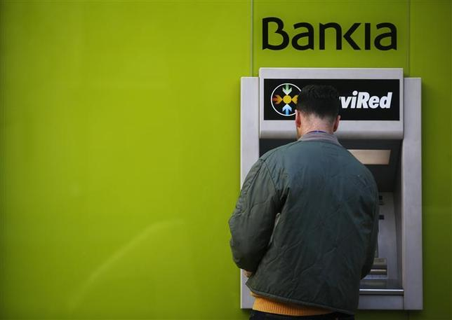 A man uses an ATM machine at a branch of Spain's nationalized lender Bankia in Madrid November 28, 2012. REUTERS/Susana Vera