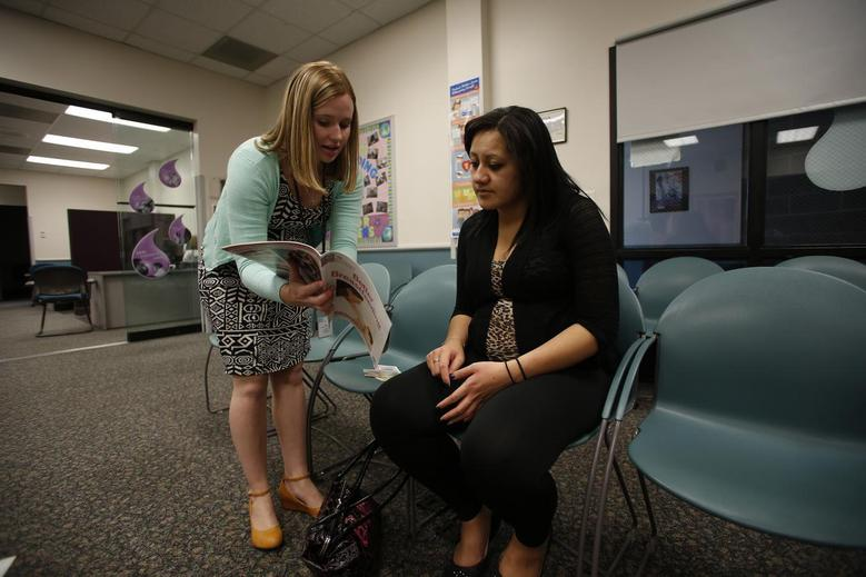 Dietician Tiffany Willard (L) teaches breastfeeding to expectant mother Kiyana Aiono at the Women, Infants and Children (WIC) office inside a Salt Lake County health clinic in West Valley City, Utah, October 2, 2013. REUTERS/Jim Urquhart