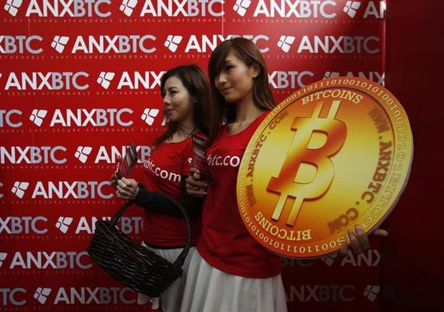 Attendants pose with a bitcoin sign during the opening of Hong Kong's first bitcoin retail store February 28, 2014. REUTERS/Bobby Yip