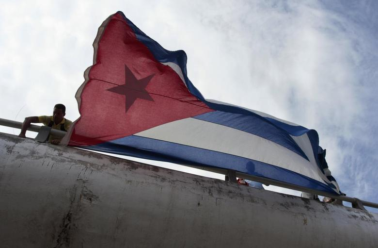Men hold a Cuban flag during an event in support of the five Cuban agents, prisoners in U.S. jails, in Havana February 27, 2014. REUTERS/Stringer
