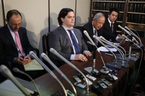 Mark Karpeles (2nd L), chief executive of Mt. Gox, attends a news conference at the Tokyo District Court in Tokyo February 28, 2014. Mt. Gox, once the world's biggest bitcoin exchange, filed for bankruptcy protection on Friday, saying it may have lost all of its investors' virtual coins due to hacking into its faulty computer system. Karpeles, bowing in contrition and wearing a suit instead of his customary T-shirt, apologised in Japanese at a news conference for the company's collapse, blaming 'a weakness in our system.' REUTERS/Yuya Shino
