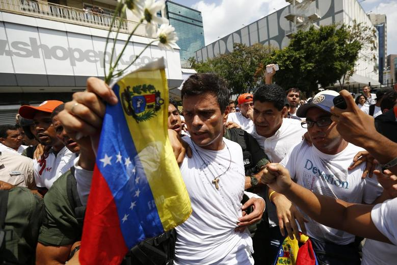 Venezuelan opposition leader Leopoldo Lopez is escorted by supporters before handing himself over in Caracas February 18, 2014. REUTERS/Jorge Silva