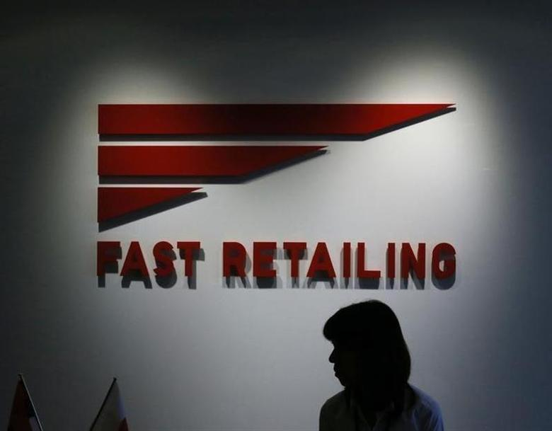 An employee of Fast Retailing Co, operator of the Uniqlo budget fashion chain, is silhouetted in front of its logo at its headquarters in Tokyo October 16, 2012. REUTERS/Kim Kyung-Hoon
