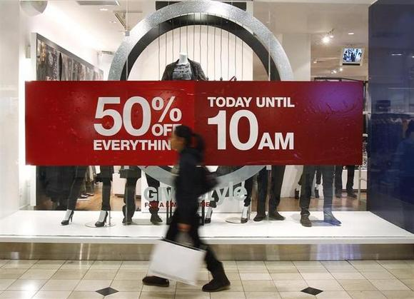 A woman walks by a store's discount advertisement inside the Roosevelt Field Mall in Garden City, New York November 26, 2010. REUTERS/Shannon Stapleton/Files