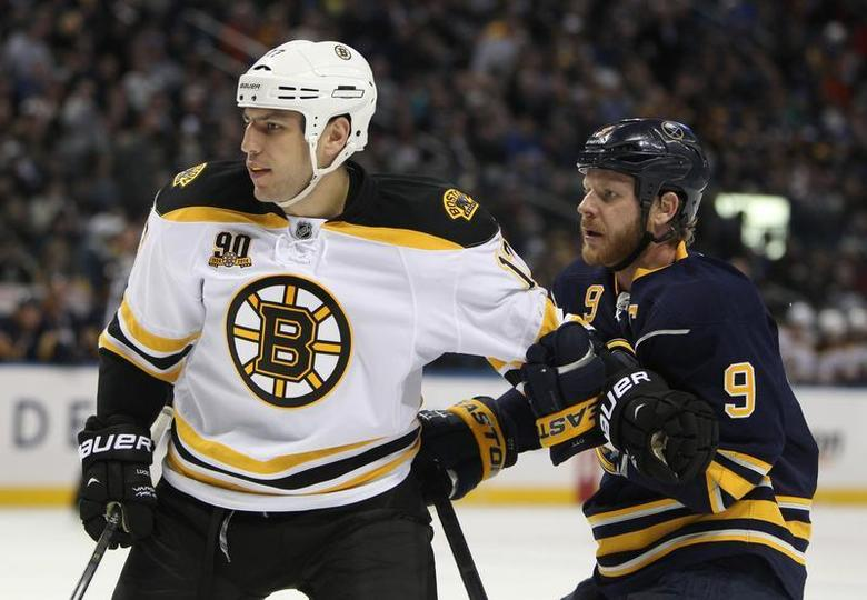 Feb 26, 2014; Buffalo, NY, USA; Boston Bruins left wing Milan Lucic (17) and Buffalo Sabres center Steve Ott (9) battle for position during the third period at First Niagara Center. Mandatory Credit: Timothy T. Ludwig-USA TODAY Sports