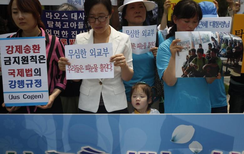 A young girl stands between protesters from a human rights group during a rally against what the U.N. believes is the recent repatriation of nine North Korean defectors from Laos, in front of the Foreign Ministry in Seoul June 5, 2013. REUTERS/Kim Hong-Ji
