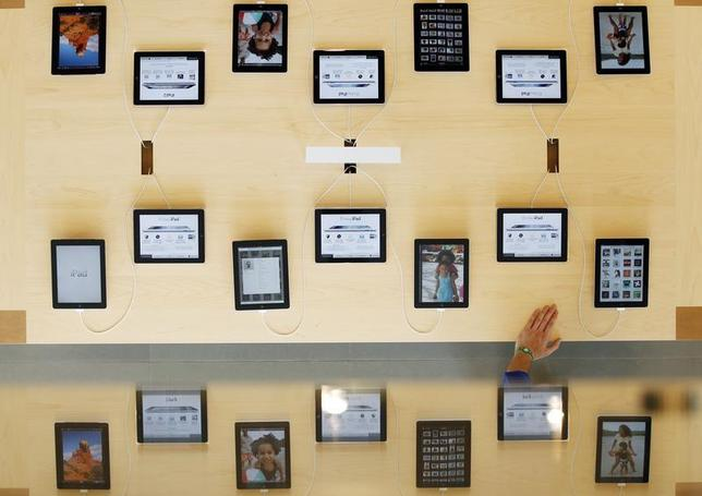 An employee rests a hand on a table displaying iPads as part of the display is reflected on a glass surface at the Passeig de Gracia Apple store in Barcelona July 26, 2012. REUTERS/Albert Gea