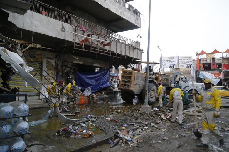 Municipal workers clean up the site of a car bomb attack in Baghdad's Karaada district February 26, 2014. REUTERS/Thaier al-Sudani