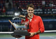 Roger Federer of Switzerland holds the trophy after defeating Tomas Berdych of the Czech Republic in their men's singles final match at the ATP Dubai Tennis Championships, March 1, 2014. REUTERS/Ahmed Jadallah