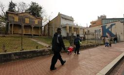 Pedestrians pass shuttered buildings in Ward 8 of Washington November 20, 2012. REUTERS/Kevin Lamarque