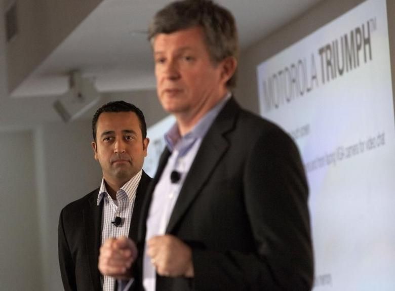 Product Chief at Sprint, Fared Adib (L) watches on as Motorola Senior Vice President of Product Development, Alain Mutricy speaks at the launch of the Motorola PHOTON 4G Summer and the Motorola TRIUMPH Virgin Mobile Summer in New York June 9, 2011. REUTERS/Andrew Kelly