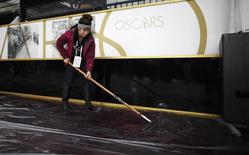 A worker brushes water off the red carpet during preparations for the 86th Academy Awards in Hollywood, California, March 1, 2014. REUTERS/Lucy Nicholson