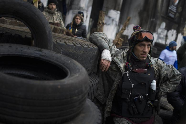 A member of the ''Maidan'' self-defense battalion listens to speeches at the site of recent street battles near Independence Square in Kiev March 1, 2014. . REUTERS/Thomas Peter