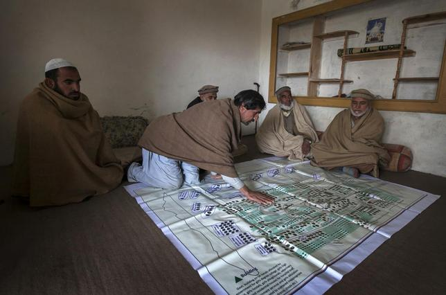 Local elders point to their fruit orchards on a map showing lands, taken over by the army for a base, in the town of Khwazakhela in the northwestern Swat valley February 4, 2014. REUTERS/Faisal Mahmood