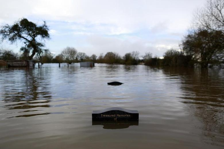 Gravestones are partially submerged in water in the flooded Somerset village of Moorland February 13, 2014. REUTERS/Cathal McNaughton