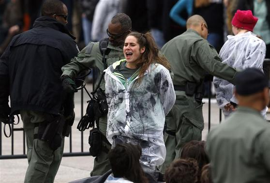 An environmental activist sings and cheers as she and others are detained as they hold a rally in opposition to the Keystone XL Pipeline on the sidewalk in front of the White House at the White House in Washington March 2, 2014. REUTERS-Jonathan Ernst