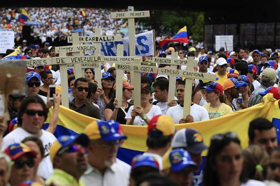 Anti-government protesters hold crucifixes with names of victims of violence during a rally against Venezuela's President Nicolas Maduro government in Caracas March 2, 2014. REUTERS-Tomas Bravo