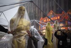 """Una cubierta estatua de los Oscar es trasladada por la alfombra roja antes de los Premios de la Academia en Hollywood. 2 de marzo. REUTERS/Adrees Latif. Muy al estilo de Hollywood, los premios de la Academia del domingo prometían tensión en la carrera por el Oscar a mejor película entre """"12 Years a Slave"""" y """"Gravity"""", pero además un final feliz luego de que amainó un aguacero de tres días."""