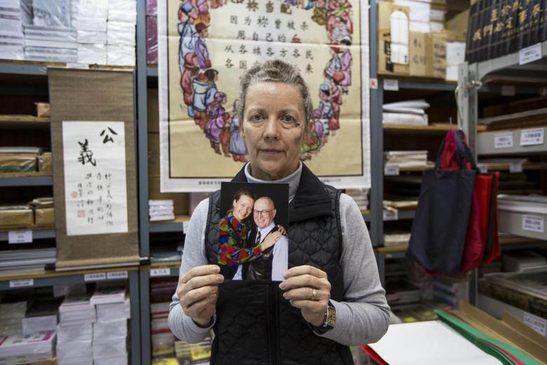 Karen Short, wife of Australian missionary John Short, poses with a photo of her husband inside the Christian Book Room in Hong Kong February 20, 2014. REUTERS/Tyrone Siu