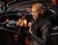 """John Ridley recebe o Oscar de melhor roteiro adaptado por """"12 Anos de Escravidão"""", em Los Angeles, nesta segunda-feira. 03/03/2014 REUTERS/Lucy Nicholson"""