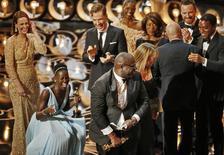 """Steve McQueen (al centro), director y productor de """"12 Years a Slave"""", celebra junto a Lupita Nyong'o (izquierda) y el resto del elenco de la cinta luego de ganar el Oscar a mejor película en la octogésima sexta entrega de los premios de la Academia de Artes y Ciencias Cinematográficas de Estados Unidos en Hollywood, California, 2 de marzo del 2014. REUTERS/Lucy Nicholson"""